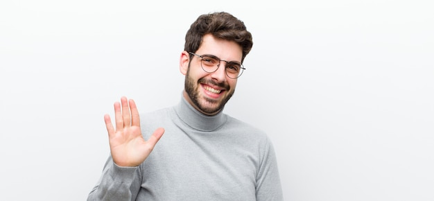 Man smiling happily and cheerfully, waving hand, welcoming and greeting you, or saying goodbye