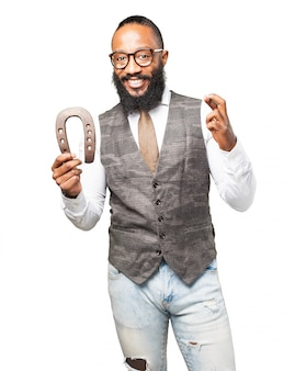 Man smiling holding a horseshoe and crossing his fingers