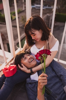 Man smiling lying on the legs of a woman with a bouquet of roses
