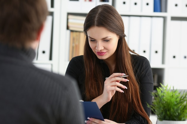 Man and smiling mature woman talking in office