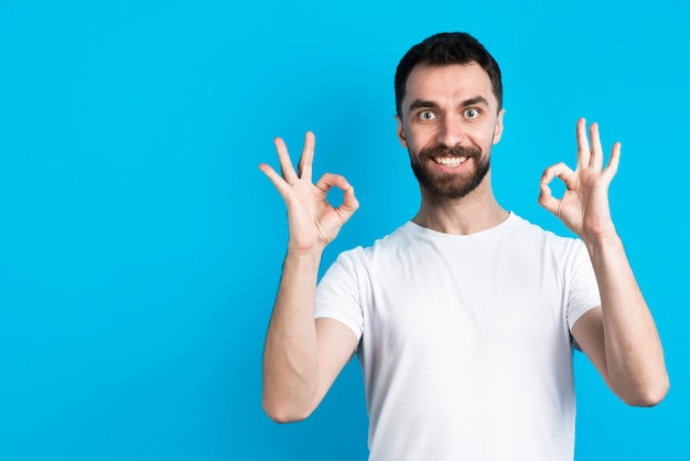 Man smiling and posing while holding okay sign