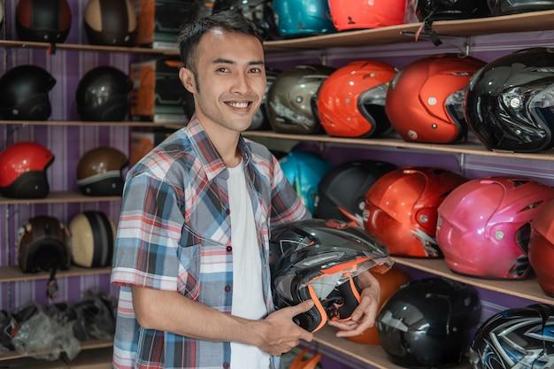 ヘルメットディスプレイラックに対してヘルメットを保持しながら立って笑っている男