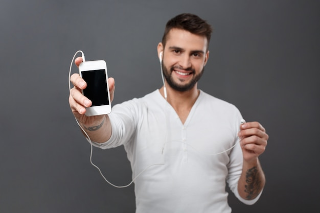 Man smiling stretching phone screen  over grey wall