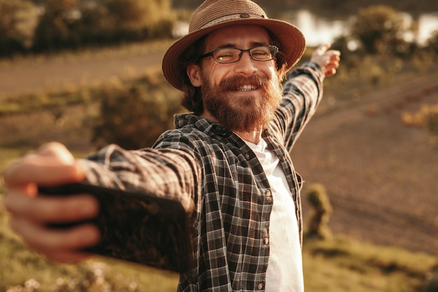 Man smiling and taking selfie for blog through countryside