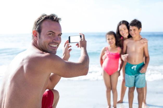 海岸で子供を撮影しながら笑顔の男