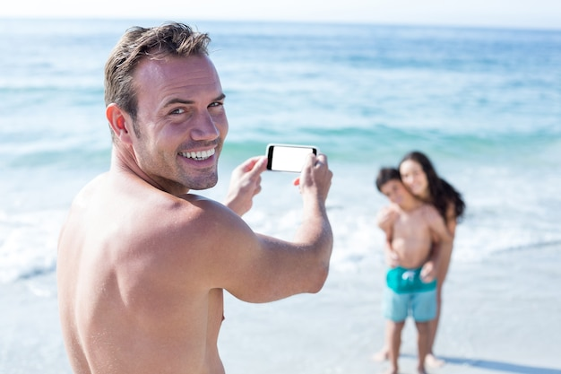 Man smiling while photographing wife and son at sea shore