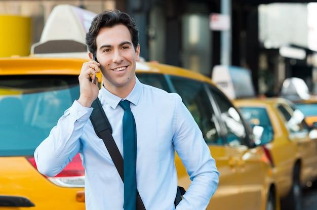 Человек улыбается во время разговора по телефону
