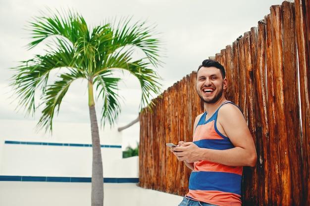 Человек улыбается, используя смартфон, стоя перед деревянным забором