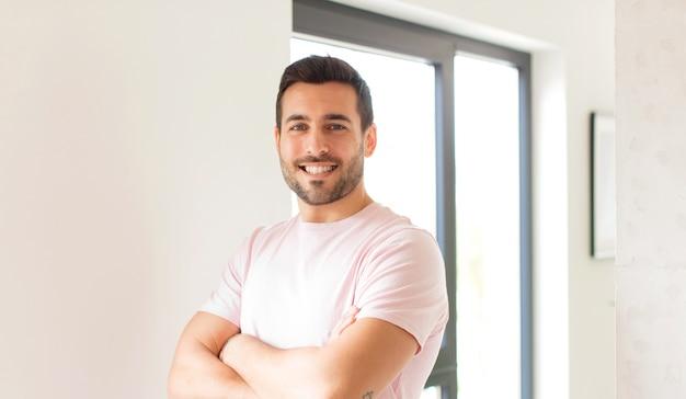 腕を組んで笑っている男と幸せで、自信を持って、満足のいく表現、側面図