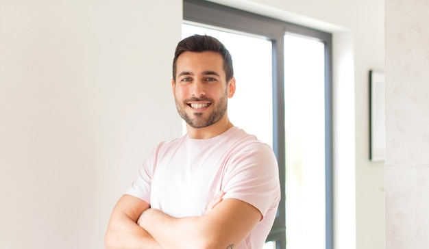 Man smiling with crossed arms and a happy, confident, satisfied expression, lateral view
