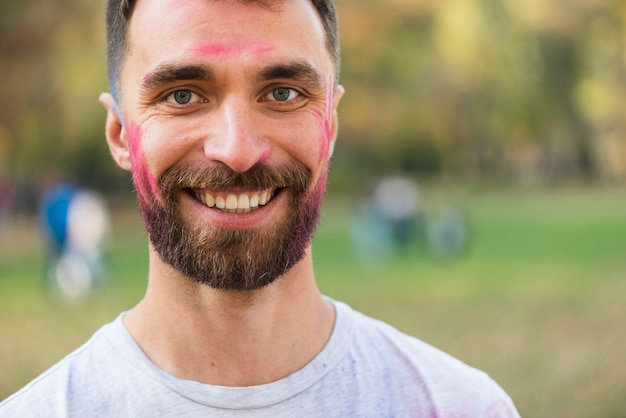 Man smiling with painted face for holi
