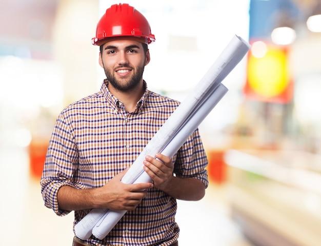 L'uomo sorridente con un casco rosso e alcuni schemi
