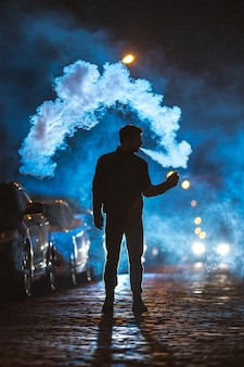 The man smoke electronic cigarette outdoor. evening night time