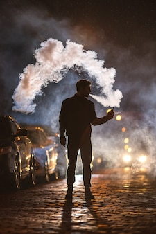 The man smoke electronic cigarette in the street. evening night time
