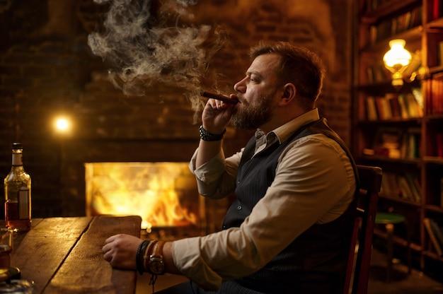 男は葉巻を吸って、背景にアルコール飲料、本棚、豊かなオフィスのインテリアを飲みます