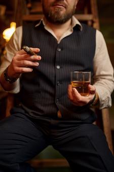 男は葉巻を吸ってアルコール飲料を飲む、背景にヴィンテージのオフィスのインテリア