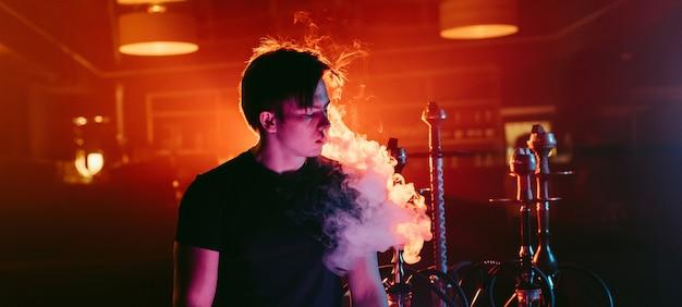 Мужчина курит кальян и выпускает облако дыма