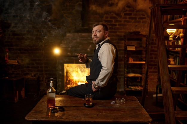 Man smokes a cigar, alcohol beverage in bottle on the table, bookshelf and vintage office interior. tobacco smoking culture, specific flavor. male smoker leisures
