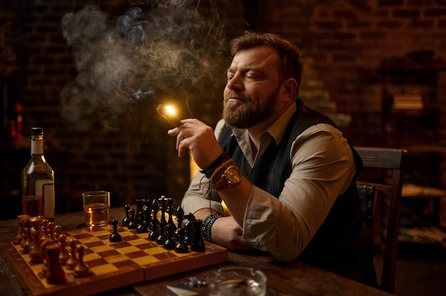 Man smokes a cigar, drinks alcohol beverage and play chess, bookshelf and vintage office interior. tobacco smoking culture, specific flavor. male smoker leisures at the chessboard