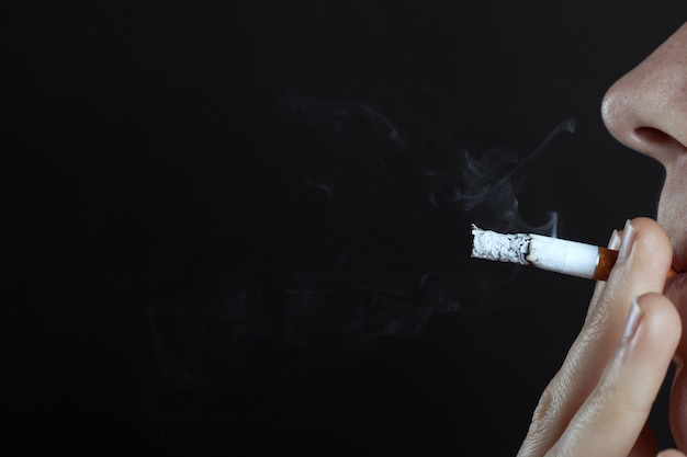 Man smokes a cigarette on a dark background close-up copy space, health hazard, harm to the body from tobacco use, bad habit.