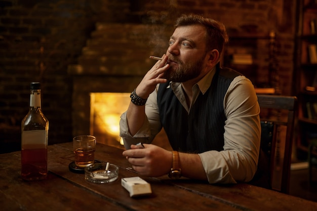 Man smokes cigarette and drinks alcohol beverage, bookshelf and rich office interior. tobacco smoking culture, specific flavor