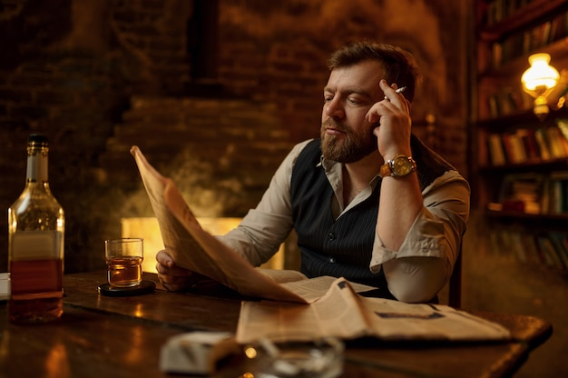 Man smokes cigarette, drinks alcohol beverage and reads newspaper, bookshelf and vintage office interior. tobacco smoking culture, specific flavor