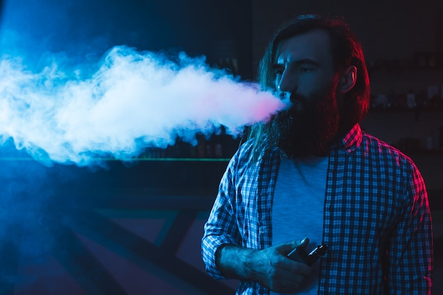 A man smokes a cigarette and lets out smoke in a nightclub.