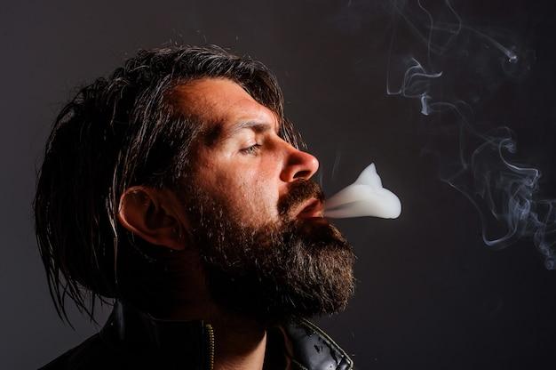 Человек курит сигарету. жестокий бородатый мужчина с сигаретой. сигаретный дым. табак.