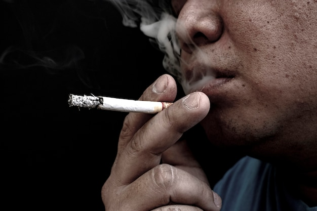 Man smoking a cigarette, image of cigarette in hand with smoke