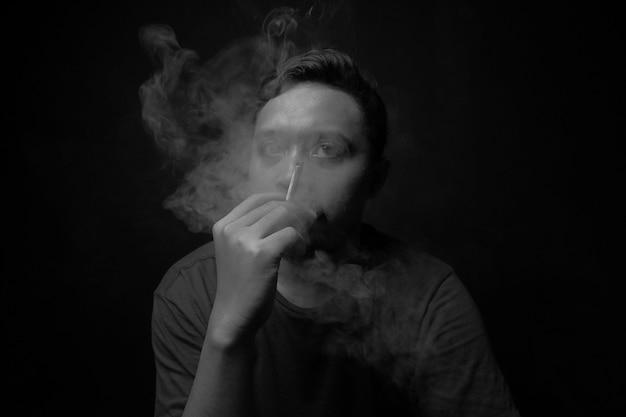 Человек курит сигарету в темноте