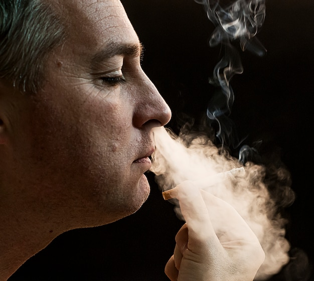 黒の背景に男の喫煙のタバコ、ハンサムな若い男の喫煙のタバコ、葉巻と黒背景に煙とミステリーの男