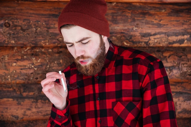 Человек курит сигарету на деревянном доме