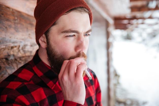 Человек курит сигарету на открытом воздухе
