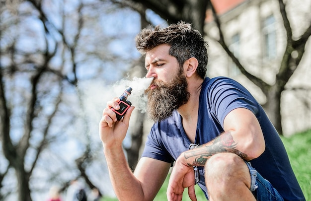 Man smoking e-cigarette. mature hipster with beard. hipster man hold vaping device. bearded brutal male smoking electronic cigarette. health safety and addiction. inhaling vapor. rugged and manly.