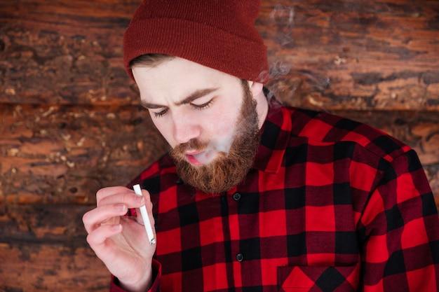Человек курит на деревянном доме