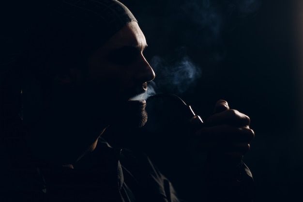 Man smoking a pipe on dark. profile portrait back lit.