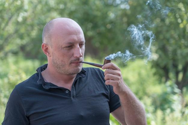 자연 백그라운드에서 남자 흡연 파이프입니다. 야외에서 중년 남자의 초상화입니다. 나쁜 습관, 중독. 건강에 해로운 라이프 스타일 개념