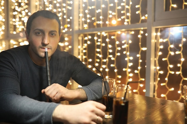 夜のカフェで水ギセルのパイプを吸う男