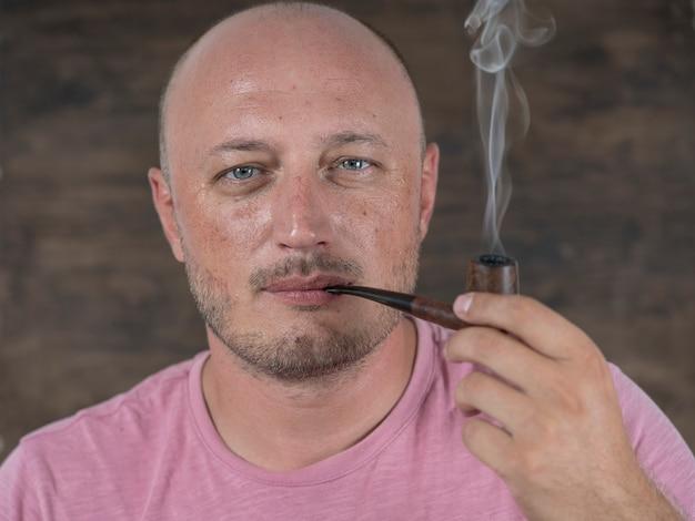 남자 담배 파이프입니다. 실내 중년 남자의 초상화입니다. 나쁜 습관, 중독. 건강에 해로운 라이프 스타일 개념입니다. 확대