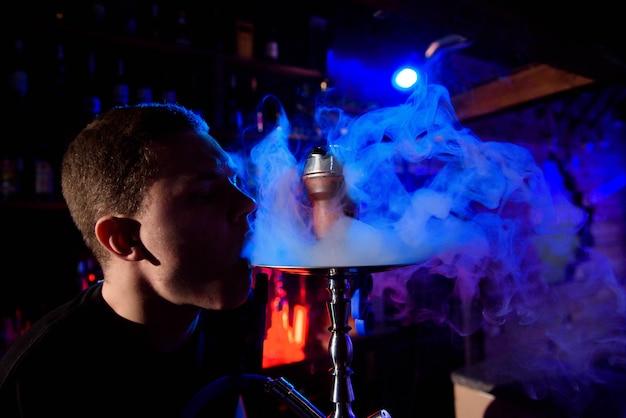 伝統的な水ギセルパイプを喫煙し、水ギセルカフェで煙を吐き出す男。