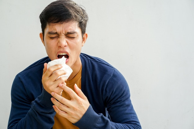 Man sneezing after get allergy or flu virus and using tissue paper for swipe on nose
