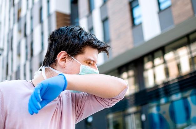Человек чихает в локте на улице, защищающей от covid-19.молодой человек с защитной одеждой в городе во время вируса короны.