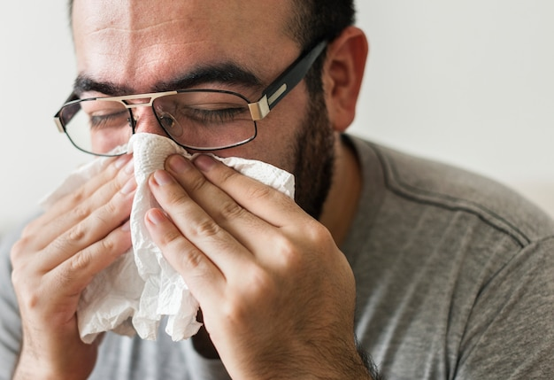 Man sneezing into tissue paper