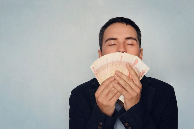 달러를 킁킁거리는 남자. 달콤한 돈 냄새. 5000 루블을 킁킁 거리며 젊은 남자가 돈을 벌었습니다. 샐러리. 쉽게 벌리는 돈. 돈 뭉치