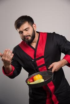 Man sniffs vegetables on dark pan .