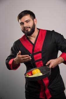 Мужчина нюхает овощи на темной сковороде.