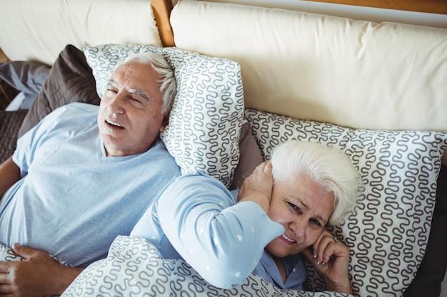 Мужчина храпит и женщина закрывает уши во время сна на кровати