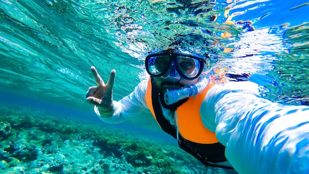 A man in snorkeling equipment and a protective vest swims on the surface of the sea.