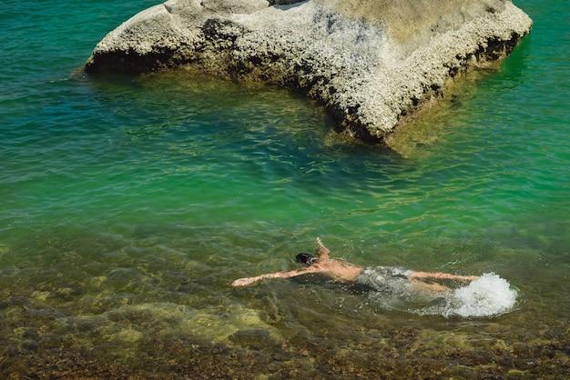 Мужчина занимается сноркелингом в чистой морской воде в таиланде на острове панган. люди живут здоровой жизнью и отдыхают в тропических странах. мальчик лежит на волнах и смотрит на рыбу