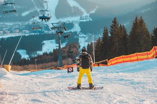 斜面の頂上で男スノーボーダー。美しい冬の山々。冬休み。コピースペース。エクストリームスポーツ
